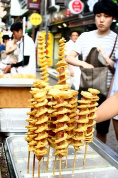 Hot dog potato on a stick - Located in Seoul are special kinds of street foods. Heres one that's a deep fried potato combined with a hot down on a stick. Who said you can't have the best of both worlds? Delightful!