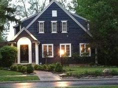 Navy blue house exterior, white trim, black door and shutters