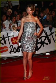 in a silver strapless stone sequin minidress by Kaufman Franco, Christian Louboutin peep-toes, a Judith Leiber clutch and David Yurman silver hoops at the 2009 Brit Awards