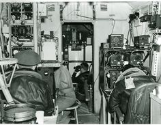 Crew members of the U.S. Navy Airship Squadron 24 looking out to the horizon, many crewmen are in the airship crew cabin.