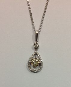 18ct white gold and diamond drop pendant featuring a centre 0.40ct 'champagne' diamond.