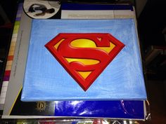 I cut a the superman logo from a $1 Target superhero bag. I used an 8x10 canvas, coated it with mod podge after painting it blue, and put one more layer of mod podge over the logo. Perfect for wall decoration in my school library.