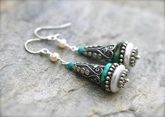 These gorgeous one of a kind statement earrings are made with large freshwater coin pearls and turquoise gemstones with Bali sterling silver spacer beads. Large cone shaped artisan Bali bead caps are wire wrapped on top of the pearl and turquoise. These will add a unique look to any outfit.