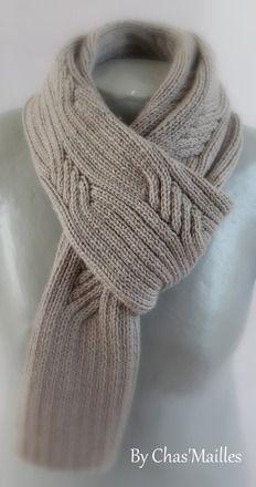 écharpe en fils 52% laine et 48% acrylique de couleur gris clair;elle est travaillée à l'aiguille.Elle accueille des torsades  finement travaillées sur une base de côtes . El - 12312027