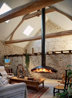 just love the suspended fireplace and stone wall with exposed timber beams