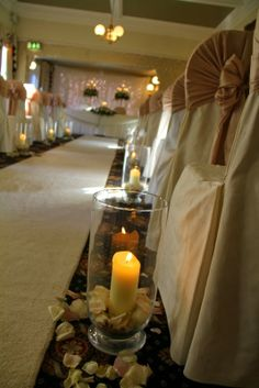 Fresh fragrant Rose Petals and large candlelit Hurricane Lamps lined the aisle