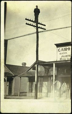 Man standing on top of a light pole in Cairo, Illinois - date unknown.