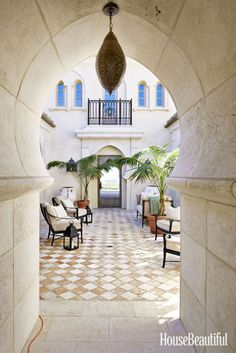 A central courtyard serves as an enticing indoor-outdoor space for the Spanish-style house. Davies-Gaetano chose a sofa and chairs from Century Furniture's Andalusia Collection that marry well with the wrought-iron parapet. Hurricanes are from her store, Bliss Home and Design. Floor tiles are antique French terracotta.