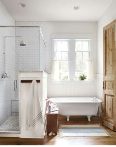 Cute old fashioned claw foot tub, wood floors and modern walking shower with subway tile floor to ceiling. Cottage farmhouse