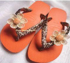 Chinelo Havaiana cor Laranja, tecido de oncinha e uma flor na cor Bege com o miolo laranja. R$ 43,00