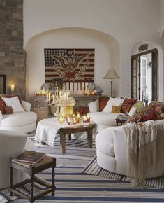 Blue-and-white rugs are casually overlapped, New England style, in this living room furnished with white slipcovered love seats. An arch-shaped niche is the perfect spot to display an antique version of Old Glory