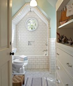 Attic bathroom, waterfall shower head... I love how the tile goes all the way around the shower up the ceiling.