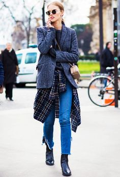 A gray blazer is paired over a gray sweater, crossbody mini bag, flannel, frayed jeans, and black boots