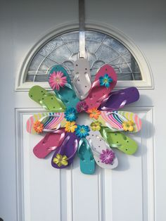 "Flip Flop Bright Sun Fun, Decorate your door or room with the summer footwear we love to wear. This wreath is fastened with greening pins making it sturdy and heat resistant. The wreath measures approximately 22"" across, includes 12 youth flip flops and comes with a variety of flower embellishment's. Please avoid displaying this wreath in between a storm and house door. Too much direct sunlight causes extreme heat built up."