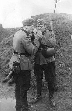 Two German soldiers sharing a light, Second World War.