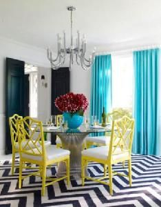 Jonathan Adler dining room    white and navy blue zigzag chevron herringbone rug, yellow faux bamboo Jonathan Adler Chippendale Chairs, chandelier, turquoise blue silk window panels curtains, glossy black doors and Worlds Away Powell Dining Table