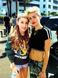 Ariana Grande and Miley Cyrus. Ariana is wearing a packer sweatshirt. Love her even more.