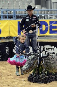 Rodeo Royalty. All Around Champion Cowboy, Trevor Brazile watches his daughter Style rope an alligator