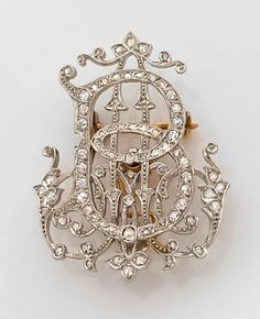 A 1900 diamond, platinum and gold monogram brooch. ~b~