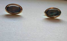 """Cufflinks in shell, dark Mother of Pearl. Oval vintage dark grey MOP cuff links in gold tone metal.  Stamped on the reverse """"Imitation"""" (which was an accessories brand).  These stylish vintage cufflinks are likely to date from the 1970s, they are approximately ¾"""", 2 cm long and in good vintage condition. See more distinctive vintage accessories for you & your home http://www.etsy.com/uk/shop/GleamingKist?section_id=13587842 and other lovely vintage items at h..."""