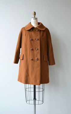 Vintage 1960s cognac wool coat with rounded collar, double breasted buttons, a-line shape, flap pockets and satin lining.  --- M E A S U R E M E N T S ---  fits like: small/medium shoulder: 18 bust: up to 42 waist: free hip: free sleeve: 20 length: 31 brand/maker: Melaire condition: really