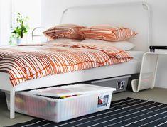 Zwei GIMSE Bettkästen in Weiß unter einem DUKEN Bettgestell in Weiß und bunter Bettwäsche darauf. Einer der Bettkästen ist hervorgezogen.