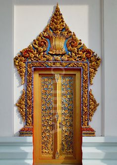 Ornate door at the entrance to a temple at Sing Buri, Thailand.  Sort of looks like it has it's hands on it's hips. :)