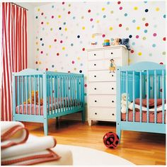This lovely little room for two is so simple, but lovely wallpaper and bright coloured cribs add interest.