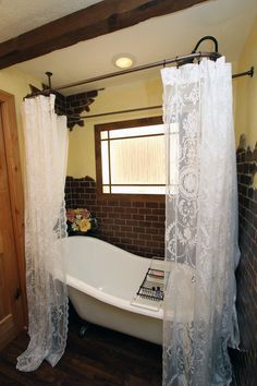 Just lovely, talk about a hideaway-- antique tub with lace shower curtain