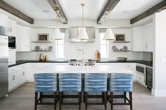 This cozy kitchen features pendant lighting over an island bar, unique blue bar stools, stainless steel appliances, a wine fridge, and beautiful white cabinetry.