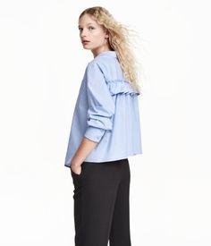 En vid blus i bomullspoplin med dekorativ volangkant bak. Blusen har en bröstficka, knäppning fram och är lätt rundad nedtill. Lång ärm.