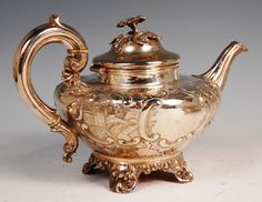 1855 ~ A mid Victorian silver teapot, of squat baluster form, repousse decorated in the Roccoco style with opposing landscape and vacant reserves.  Made by James & Josiah Williams, Exeter, England