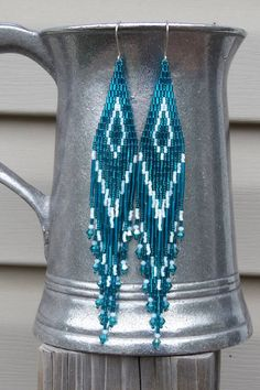 Shoulder duster fringe earrings - handmade by me. * 6 1/8 Long - 7/8 Wide * Ear Wires are Silver-Filled * Galvanized Blue Zircon/Teal and Matte Opaque White Colors * Fringe includes matching 3mm Swarovski Crystal * Ready to Ship - Rush Shipping Available During Check-out The pattern was created by Suzanne McNeill and is done in what is called a cheyenne or a brick stitch. Thanks for looking! I invite you to check out my shop to see other bead-woven and quill items…