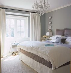 bed sheets same color as wall, chandelier, white duvet and white bedskirt.