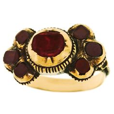 Georgian Garnet & Tourmaline Finger Ring in Gold. Circa 1800, 15k, attrib. Austro-Hungarian. This striking Georgian ring features smoldering red garnets framing a bordeaux-colored tourmaline center stone. An evocative example of period jewelry, this type of ring was extremely popular in the late 18th and early 19th centuries. With its distinctive early closed-back bezel settings and soft coppery toned gold, the look is old world chic.