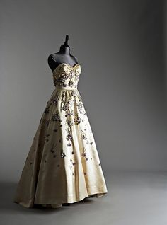 An important Pierre Balmain ball gown and matching evening coat, Autumn/Winter 1955, labelled and indistinctly numbered, the boned, strapless bodice with ruched folds of ivory satin emphasising the curves of the breast in contrast to the tiny, fitted waist and enormous satin skirt with five internal layers of silk, tulle and horsehair petticoats, embroidered and appliquéd overall with scattered bunches of violets, the petals formed from organza florets in shades of purple silk, degradé…