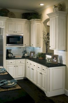 Kitchent Cabinets Makeover Lovely, quaint kitchen with dark, wood stain floors, black granite counters, raised panel cabinets and a white tile backsplash. Distressed Kitchen Cabinets, Antique White Cabinets, Diy Kitchen Cabinets, Kitchen Redo, New Kitchen, Kitchen Ideas, Black Granite White Cabinets, Kitchen Black, Kitchen Designs