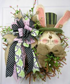 A sweet rabbit with a striped top hat and burlap bow in muted greens, black and pink sets the stage for this design. The large Terri Bow with designer quality ribbon coordinates with the theme. Measur