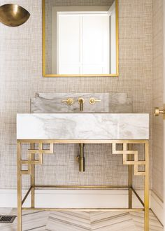 The powder bathroom (which we are particularly proud of!) includes a custom brass vanity with a calcutta top. The dreamy wallpaper is by Quadrille and the sconce is by RH | Coats Homes | Highland Park, TX