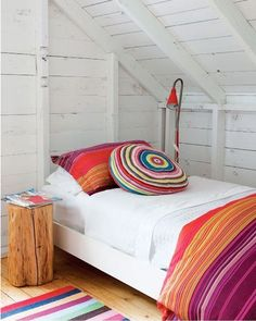 Gorgeous little boho guest bedroom. Vibrant colours, cool tree stump side table.