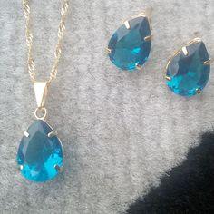 Conjunto folheado a ouro 18k com cristal azul. Contém: Gargantilha com pingente de cristal azul. Par de brincos com cristal azul.