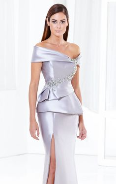 Be at your best with Terani Couture Evening E3778. A lovely evening gown in satin. The fitted bodice features and an asymmetrical off the shoulder neckline and a mid cut back. Beads adorn the bodice while the pleated peplum detail finishes off the style.