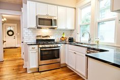 As seen on Rehab Addict, the kitchen in the Riley home was completely gutted. New cabinets, appliances and granite countertops were added. A white subway tile backsplash with dark-colored grout adds a vintage touch. In order to keep something from the original home, Nicole Curtis was able to salvage the hardwood floors.