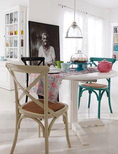 Die gemütlichen Stühle haben eine geflochtene Sitzfläche und sind antik gestrichen.