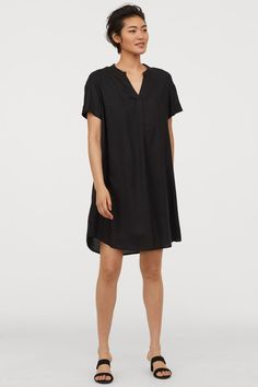 Short straight-cut dress in woven fabric. Small stand-up collar V-neck opening at top dropped shoulders and short sleeves with sewn foldover cuffs. Rounded hem slightly longer at back. Fashion Art, Spring Fashion, Fashion Beauty, Girl Fashion, Pretty Black Dresses, Straight Cut Dress, Fashion Company, V Neck Dress, Lady
