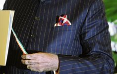 A close-up view of Indian Prime Minister Narenda Modi's dark pinstripe suit, repeatedly embroidered with the words