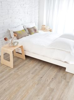 White stone walls and light beachy hardwood floors.   relaxing white bedroom <3