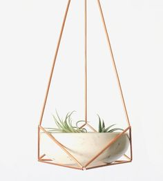 "This set includes a copper himmeli hanging planter and ceramic bowl handcrafted by JociePots. The word ""himmeli"" derives from the Swedish word ""himmel"" which means ""sky"" or ""heaven"" - perfect, given the beautiful geometric pattern this pretty thing casts on the wall in the right light. The ceramic bowl can be easily removed and placed back inside, which makes it the perfect spot to perch and water air plants and succulents."