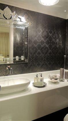 Lavabo com papel de parede em tons de cinza e bancada branca. Espelho veneziano arremata o decor. Projeto de decoração e design de interiores para apartamento em São Paulo.