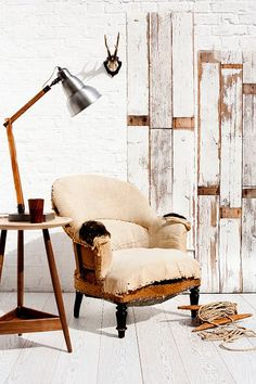 Loving the white brick wall and rustic wooden panels. Not to mention the awesome lamp and armchair!